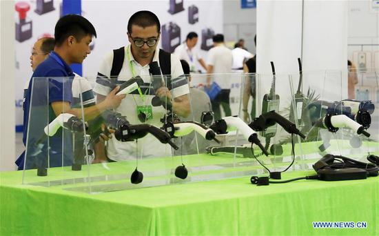 A visitor (R, front) looks at charging devices during the 2019 Shanghai International New Energy Vehicle Industry Expo in east China's Shanghai Municipality, Aug. 28, 2019. The three-day event opened at Shanghai New International Expo Center on Wednesday with the participation of over 500 global exhibitors. (Xinhua/Fang Zhe)