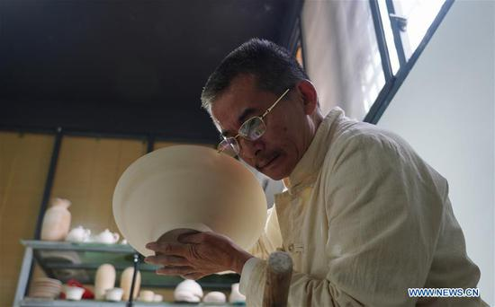 Xiong Guoan listens to the tapping sound of an unburnt porcelain bowl to judge its thickness in Jingdezhen, east China's Jiangxi Province, Oct. 28, 2019. Xiong Guoan, an inheritor of thin body porcelain in Jingdezhen of Jiangxi, learnt the art from his father when he was 12 years old. Working in the field for 47 years, he insists for perfection in the making procedures. The shaping of the unburnt porcelain is the essence of the craft, during which craftsman will use tools to peel the unburnt porcelain until it can be penetrated by the light. Xiong's skill has allowed him to make thin body porcelain with a thickness of about 0.15 millimeter. (Xinhua/Zhou Mi)