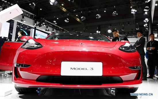 Visitors view a Tesla Model 3 during the 18th Shanghai International Automobile Industry Exhibition in Shanghai, east China, April 17, 2019. (Xinhua/Fang Zhe)