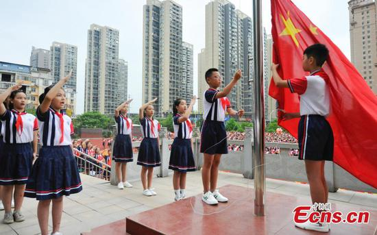 Pupils hold a flag-raising ceremony at Yushui No. 6 primary school in Jiangxi Province, Sept. 1, 2019. New semester began in China. (Photo/China News Service)