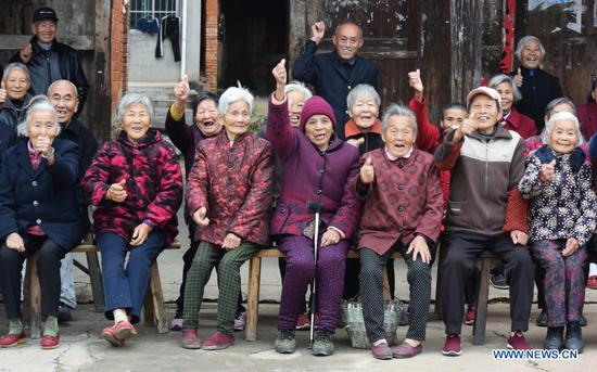 Villagers pose for a group photo in Shangwei Village of Youlan Town, Nanchang City, east China's Jiangxi Province, Nov. 22, 2020. Since 2014, volunteers from a non-profit organization in Nanchang City have kept on taking photos of smiling faces of farmers aged over 70 years old in nearby villages. The portait photos taken by volunteers were given to farmers for free. By far, the volunteers have taken nearly 4,350 people and 50,000 photos. They aim at collecting high-definition images of 10,000 farmers within 10 years. (Xinhua/Chen Chunyuan)