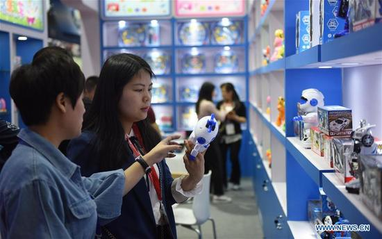 Visitors look at a toy product during the 30th Guangzhou International Toy & Hobby Fair at PWTC Expo in Guangzhou, south China's Guangdong Province, April 8, 2018. Nearly 4,000 exhibitors will showcase their latest toy and hobby products during the three-day event which opened here on Sunday. (Xinhua/Lu Hanxin)