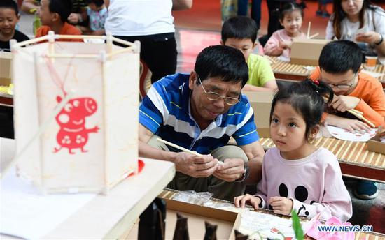 Young citizens make lanterns in an event held to celebrate the Lantern Festival in Hainan Museum in Haikou, the capital of south China's Hainan Province, Feb. 19, 2019. Traditional games as children's rhyme reading, riddle guessing and lantern making are provided in the event. (Xinhua/Yang Guanyu)
