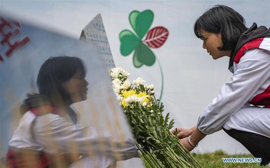 A volunteer lays flowers in front of a monument in honour of organ donors during a commemorative event held at a human organ donor memorial park in Kunming, southwest China's Yunnan Province, April 3, 2019. The human organ donation work was officially launched in Yunnan Province in July 2013. By the end of March 2019, 333 organ donation cases have been recorded and the number of registered organ donation volunteers has reached 6,398. (Xinhua/Jiang Wenyao)