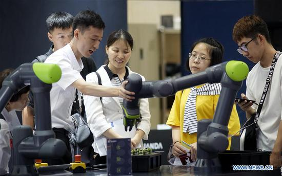A staff member introduces an intelligent manipulator to visitors during the 2019 World Robot Conference in Daxing District of Beijing, capital of China, Aug. 20, 2019. The 2019 World Robot Conference, themed