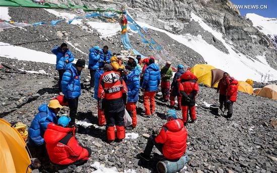 Team members are seen at the advance camp at an altitude of 6,500 meters on Mount Qomolangma, May 18, 2020. A Chinese mountaineering team on Monday released a list of 12 people, including two surveyors, who will climb to the peak of Mount Qomolangma. If everything goes smoothly, they will arrive at the peak on May 22 to conduct surveys in gravity, global navigation satellite systems, weather and depths of ice and snow. Chen Gang and Wang Wei, both of whom are surveyors from the Ministry of Natural Resources, are on the list. If either of them manages to arrive at the peak, it will set a record for Chinese surveyors setting foot on the world's highest mountain peak, according to the team. The names of a support squad and a backup squad were also released on Monday. (Xinhua/Tashi Tsering)