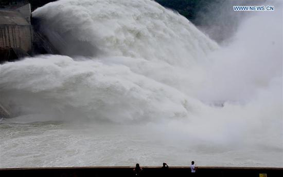 Tourists watch water gushing out from the Xiaolangdi Reservoir on the Yellow River in central China's Henan Province, July 3, 2018. The reservoir started to discharge water at 2,300 cubic meters per second Tuesday. (Xinhua/Miao Qiunao)