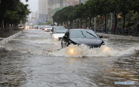 Cars run through the floodwater in Haikou, south China's Hainan Province, Aug. 10, 2018. Hainan was hit by heavy rainfalls under the influence of a tropical depression on Friday, which triggered a red alert for rainstorms in seven cities and counties, including Haikou. (Xinhua/Wang Junfeng)
