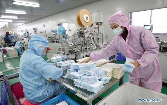 Workers make facial masks at the workshop of a company in Wuhan, central China's Hubei Province, Jan. 28, 2020. (Xinhua/Cai Yang)