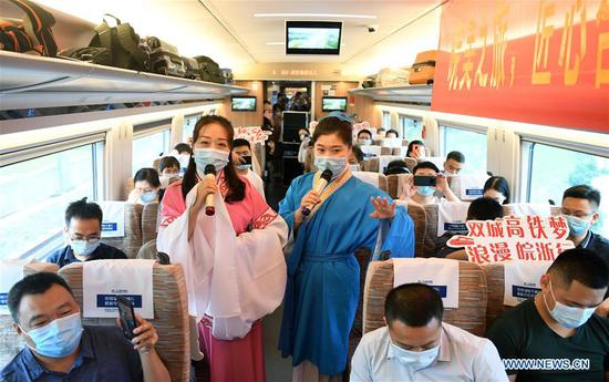 Railway staff members stage a performance aboard train No. G9394 travelling from Hefei to Hangzhou on the Shangqiu-Hefei-Hangzhou high-speed railway, June 28, 2020. A new high-speed railway route connecting east and central China started operation on Sunday. With a designed speed of 350 kph, the route connects the city of Shangqiu in central China's Henan Province, and Hefei and Hangzhou, the capital cities of east China's Anhui and Zhejiang provinces. (Xinhua/Liu Junxi)