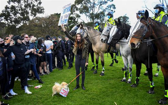 Protesters confront police at the Shrine of Remembrance in Melbourne, Australia, on Saturday, during an anti-lockdown rally against strict restrictions amid the coronavirus pandemic. Victoria state on Sunday extended a hard lockdown in its capital Melbourne until September 28. — AFP