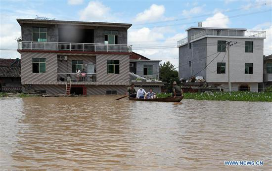 Residents take boat in flooded area in Qiaoxi Village of Maxu Township of Fuzhou City, east China's Jiangxi Province, July 8, 2018. Flood caused by heavy rain damaged crops and housings in Maxu Township and rescue groups were set up to help the affected people. (Xinhua/He Jianghua)