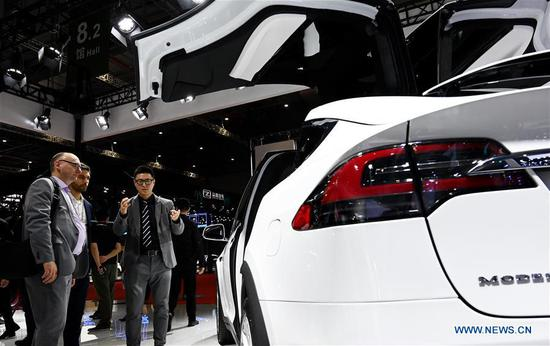 Visitors view a Tesla SUV during the 18th Shanghai International Automobile Industry Exhibition in Shanghai, east China, April 17, 2019. (Xinhua/Fang Zhe)