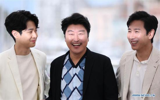 Actors Choi Woo-shik (L), Kang-ho Song and Lee Sun-kyun (R) pose during a photocall for