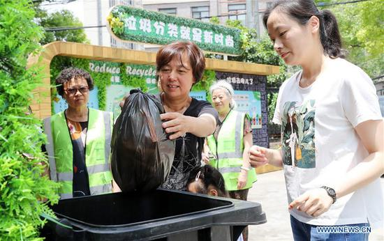 Garbage sorting volunteers help a resident to sort the garbage at a community in Hongkou District of Shanghai, east China, June 24, 2019. (Xinhua/Fang Zhe)