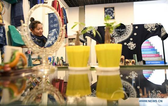 Li Andi arranges goods at her shop in Changchun, northeast China's Jilin Province, April 11, 2018. Li studied folk arts and crafts design and graduated from Jilin Agricultural University in 2006. Since 2015, she has started to research shaman culture and designed related products at her studio. She opened a maker shop in Changchun in March 2018 and wants to protect the traditional shaman culture through her product design. (Xinhua/Wang Haofei)