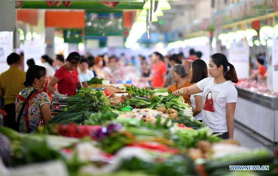 Citizens purchase vegetables at a market in Haikou, capital of south China's Hainan Province, July 11, 2018. More vegetables are supplied by Haikou Shopping Basket Industry Group Company to stabilize the price of vegetables, as Haikou entered off-season vegetable production since May. (Xinhua/Guo Cheng)