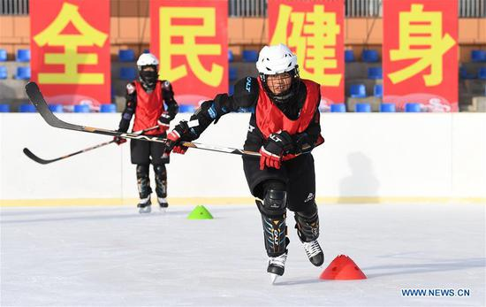 Ulis (R) of ice hockey team of Wenyun County Primary School attends a training session in Fuyun County of Altay, northwest China's Xinjiang Uygur Autonomous Region, Jan 18, 2019. Wenyun County Primary School established their ice hockey team in 2013, the first campus ice hockey team in Altay, with the help of the Charles Wang Ice Hockey Hope Project. There are 50 players aging 10 to 14 in the team at present. Altay is enhancing local winter sports and fitness programs for its rich ice and snow resources, such as ice hockey, ice soccer, skiing and skating. (Xinhua/Sadat)