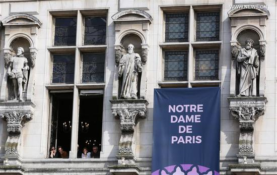 People look out of the window to see a commemoration ceremony for the cathedral Notre Dame de Paris in front of the Hotel de Ville of Paris in Paris, France, April 18, 2019. A ceremony was held in front of Hotel de Ville of Paris on Thursday to commemorate the cathedral of Notre Dame de Paris which caught fire on Monday afternoon in Paris. (Xinhua/Gao Jing)