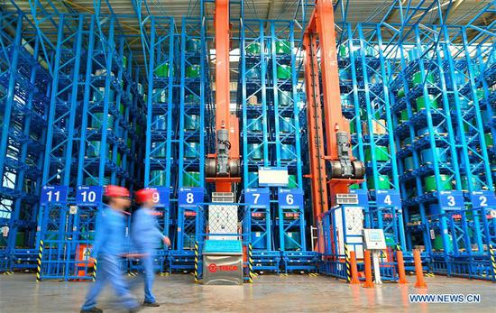 Workers of Taiyuan Iron and Steel (Group), or TISCO, walk past a stereoscopic warehouse for ultra-thin stainless steel strip in Taiyuan, north China's Shanxi Province, May 24, 2019. As a leading stainless steel maker, TISCO boasted research and development of high-tech stainless steel products by large efforts on innovation. So far TISCO possesses over 2,700 authorized patents, including 772 patents for invention. (Xinhua/Cao Yang)