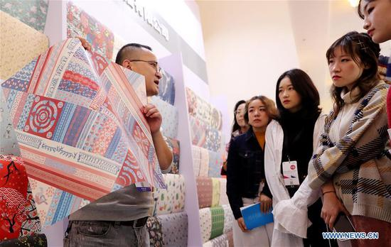 A staff member (L) introduces wrapping papers to visitors at the first Yangtze River Delta International Cultural Industries Expo (YRDICIE) in Shanghai, east China, Nov. 29, 2018. The expo kicked off here on Thursday. (Xinhua/Fang Zhe)