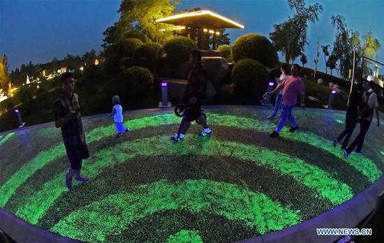 People walk on the 2.5-km fluorescent walkway at Mozishan Park in Shenyang, capital of northeast China's Liaoning Province, June 10, 2019. (Xinhua/Yang Qing)