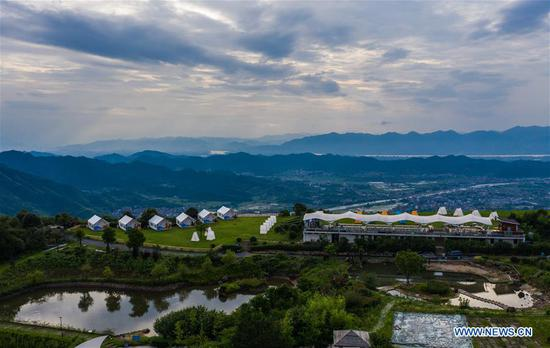 Aerial photo taken on June 27, 2020 shows a glamping resort on top of Yongan Mountain in Chang'an Township of Fuyang District, Hangzhou, east China's Zhejiang Province. Township-level governments in Fuyang District have worked in collaboration to maximize the Huyuan River's ecological resources and promote local ecotourism. (Xinhua/Xu Yu)