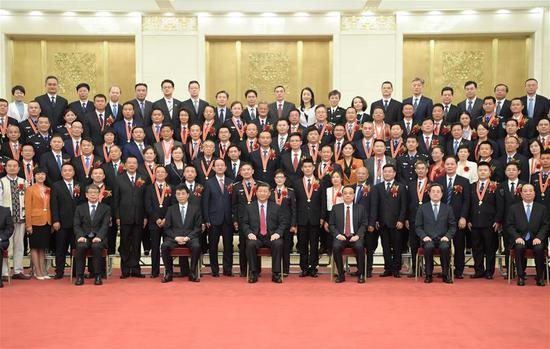 Chinese President Xi Jinping, also general secretary of the Communist Party of China (CPC) Central Committee and chairman of the Central Military Commission, poses for a group photo while meeting with representatives of model civil servants who are here to attend a national awarding ceremony in Beijing, capital of China, June 25, 2019. Premier Li Keqiang, and Wang Huning, a member of the Secretariat of the CPC Central Committee, who are both members of the Standing Committee of the Political Bureau of the CPC Central Committee, were present. (Xinhua/Li Xueren)