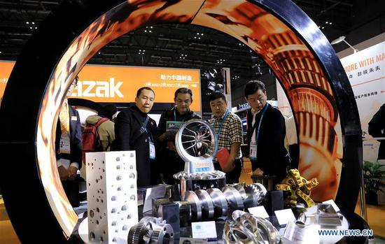 People visit the booth of Mazak at the Equipment exhibition area during the second China International Import Expo (CIIE) in Shanghai, east China, Nov. 6, 2019. The National Exhibition and Convention Center in Shanghai greeted a large number of visitors on the second day of the CIIE. (Xinhua/Fang Zhe)