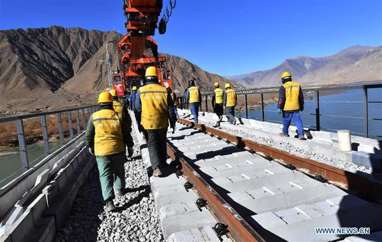 Workers of China Railway 11 Bureau Group Co., Ltd. prepare to lay steel rail for a bridge crossing the Yarlung Zangbo River of Lhasa-Nyingchi railway in Sangri County of Shannan, southwest China's Tibet Autonomous Region, Dec. 1, 2019. The rail-laying work of a 4,615-meter-long bridge crossing the Yarlung Zangbo River of Lhasa-Nyingchi railway was completed on Sunday. The Lhasa-Nyingchi railway features complex geological conditions, with a total length of 435 km, 75 percent of which are bridges and tunnels. The construction work began in 2015 and is expected to be completed in 2021. (Xinhua/Chogo)