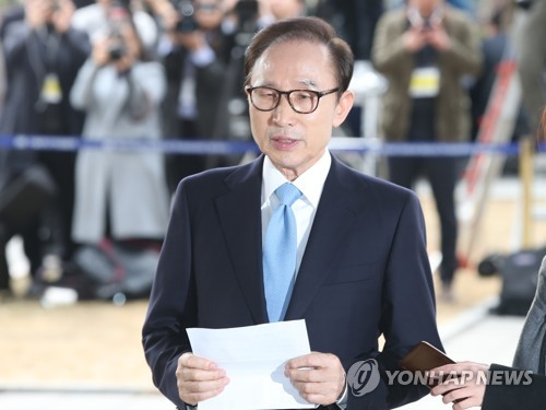 Former South Korean president Lee Myung-bak reported to prosecutors for questioning in a corruption probe Wednesday