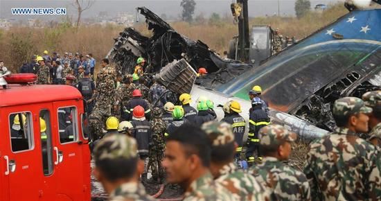 Rescuers work at the plane crash site in Kathmandu, Nepal, on March 12, 2018. At least 49 people were killed and 17 injured after a passenger plane of the US-Bangla Airlines crashed at Nepal's Tribhuvan International Airport (TIA) on Monday afternoon, authorities confirmed. (Xinhua/Sunil Sharma)