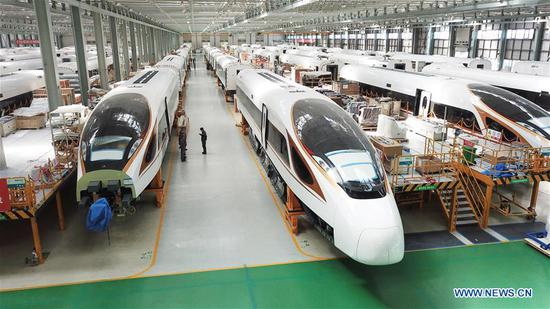 Fuxing bullet trains are seen at the assembly workshop at CRRC Changchun Railway Vehicles Co. Ltd. in Changchun, capital of northeast China's Jilin Province, Sept. 14, 2017. China's annual political sessions of the National People's Congress (NPC) and the National Committee of the Chinese People's Political Consultative Conference (CPPCC) are scheduled to convene in March, 2018. During the two sessions, development agendas will be reviewed and discussed, and key policies will be adopted. According to the 13th five-year plan for economic and social development of China covering the period 2016 to 2020, coordination has been emphasized as an integral quality of sustained and healthy development, which underlines advancing coordinated development between rural and urban areas, between different regions, and between economic and social development. (Xinhua/Zhang Nan)