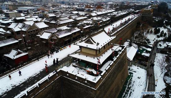Aerial photo taken on Jan. 7, 2018 shows the snow-covered ancient city wall built in Ming Dynasty in Xi'an, capital of northwest China's Shaanxi Province. After days of rain and snow, Xi'an greeted sunny weather on Sunday. (Xinhua/Liu Xiao)