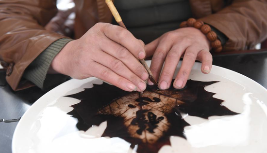 Photo taken on March 2, 2018 shows Hao Xudong carving leaves. Leaf carving, or namely painting on leaves, is a process which takes 3 days to collect, preserve, strip, pattern and carve the leaves. Hao Xudong is a former paper-cutting craftsman and has been leaf carving for 9 years, making around 100 pieces in total.