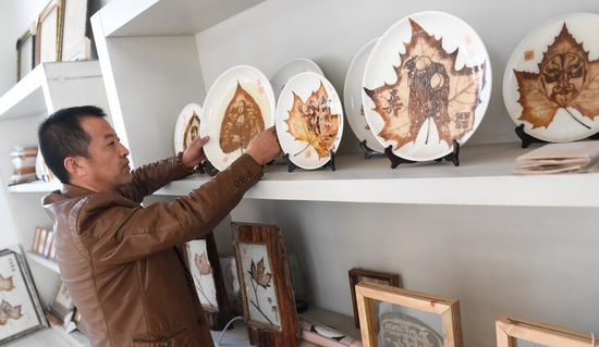 Photo taken on March 2, 2018 shows Hao Xudong exhibits his leaf carving,