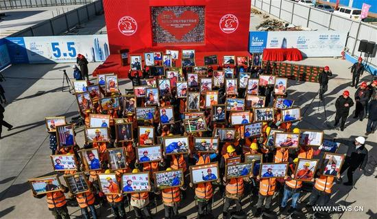 Workers pose for a group photo holding their portraits in Beijing, capital of China, Jan. 9, 2018. A team consisted of press photographers and photographic enthusiasts volunteered to make portraits for workers on their jobs from construction and other industries. More than 1,000 workers received their photos on Tuesday. (Xinhua/Li Xin)