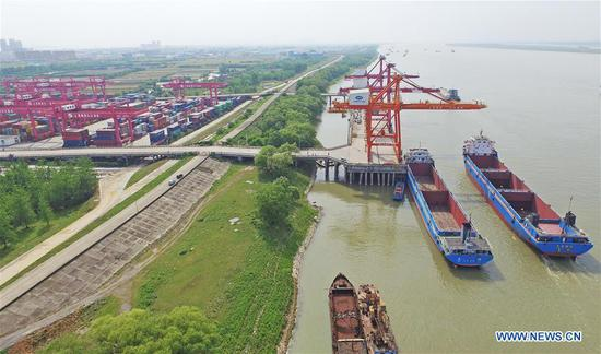 Photo taken on May 9, 2017 shows a dock of the Jiujiang Port on the Yangtze River in east China's Jiangxi Province. China's annual political sessions of the National People's Congress (NPC) and the National Committee of the Chinese People's Political Consultative Conference (CPPCC) are scheduled to convene in March, 2018. During the two sessions, development agendas will be reviewed and discussed, and key policies will be adopted. According to the 13th five-year plan for economic and social development of China covering the period 2016 to 2020, coordination has been emphasized as an integral quality of sustained and healthy development, which underlines advancing coordinated development between rural and urban areas, between different regions, and between economic and social development. (Xinhua/Wan Xiang)