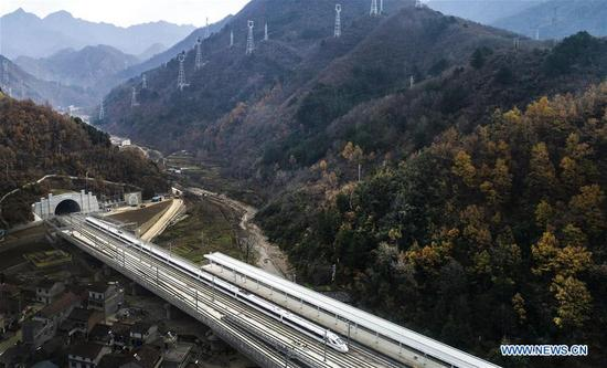 A bullet train runs into Foping Station during a trial in northwest China's Shaanxi Province, Nov. 25, 2017. High-speed trains linking Xi'an, capital of Shaanxi Province, and Chengdu, capital of Sichuan Province, will begin operation on Dec. 6, authorities said Sunday. (Xinhua/Tao Ming)