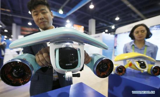 A staff member of Sublue shows WhiteShark Mix, a Chinese innovational underwater scooter, at Consumer Electronics Show (CES) in Las Vegas, the United States, Jan. 10, 2018. (Xinhua/Li Ying)