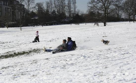 People play on grass covered with snow in London, Britain, on Feb. 28, 2018. (Xinhua/Han Yan)