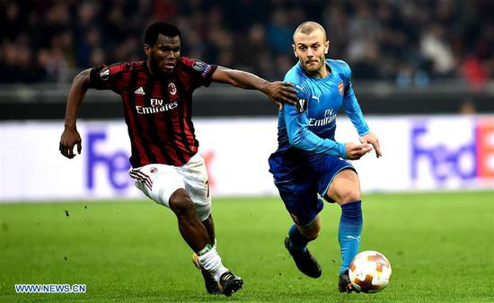 AC Milan's Frank Kessie (L) competes with Arsenal's Jack Wilshere during a Europa League round of 16 first leg soccer match between AC Milan and Arsenal at the San Siro stadium in Milan, Italy, March 8, 2018. Arsenal won 2-0. (Xinhua/Alberto Lingria)