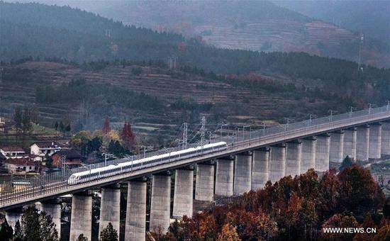 A bullet train runs on a bridge of Xi'an-Chengdu high-speed railway during a test in northwest China's Shaanxi Province, Nov. 22, 2017. The Xi'an-Chengdu line is China's first rail route to run through the Qinling Mountains, which are the natural boundary between north and south China. It will begin operation on Dec. 6. (Xinhua/Tang Zhenjiang)