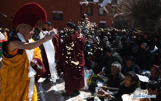 A monk spreads cooked rice to people as a kind of blessing during a religious service at the Qoide Monastery in Gonggar County of Shannan Prefecture, southwest China's Tibet Autonomous Region, March 2, 2018. (Xinhua/Chogo)