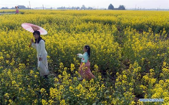 Zhao Zirong and her daughter pose for photos in the fields of rape flowers in Ranyi Township of Chengdu, southwest China's Sichuan Province, March 11, 2018. Rural tourism has been stressed as a crucial part of China's strategies of rural vitalization. (Xinhua/Jiang Hongjing)