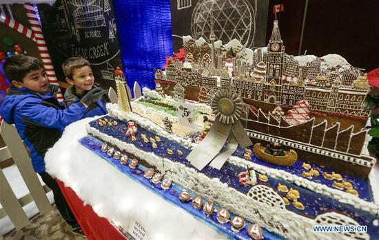 Kids admire gingerbread houses displayed at the 27th annual Gingerbread Lane competition in Vancouver, Canada, Dec. 4, 2017. A total of 33 local amateur and professional cakemakers participated in the event and showed their works to visitors. (Xinhua/Liang Sen)