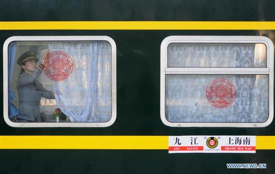 A railway crew member draws the curtain of a train carriage at Jiujiang Railway Station in Jiujiang, east China's Jiangxi Province, March 12, 2018. China's 2018 Spring Festival travel season came to an end on Monday. The period, also known as