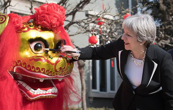 UK Prime Minister Theresa May 'dots the eye' of a Chinese dragon, a traditional ritual of awakening a dragon, on the grounds of the UK Embassy in Beijing on Feb. 1. Photo: VCG