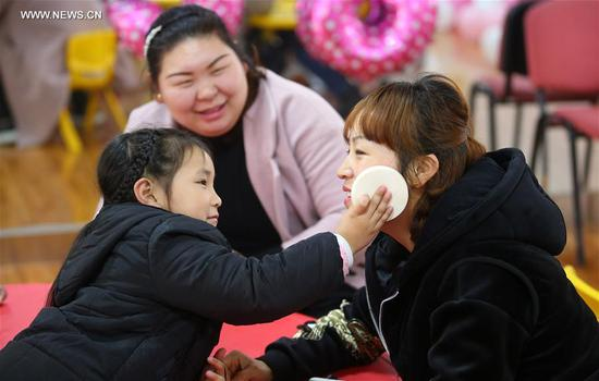 A child puts on makeup on her mother during an activity ahead of the International Women's Day at Lidu community in Nantong City, east China's Jiangsu Province, March 6, 2018. (Xinhua/Xu Peiqin)