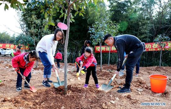 Children shovels oil under the guidance of their teachers and parents during a treeplanting activity at Lijiaxiang Township of Changxing County, east China's Zhejiang Province, March 12, 2018. A tree planting activity aimed at fostering children's awareness about environmental protection was held here. (Xinhua/Xu Xu)
